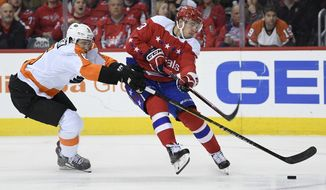 Philadelphia Flyers defenseman Travis Sanheim (6) battles for the puck against Washington Capitals left wing Jakub Vrana (13), of the Czech Republic, during the second period of an NHL hockey game, Tuesday, Jan. 8, 2019, in Washington. The Capitals won 5-3. (AP Photo/Nick Wass)