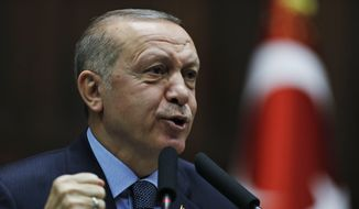 """Turkey's President Recep Tayyip Erdogan delivers a speech to MPs of his ruling Justice and Development Party (AKP) at the parliament in Ankara, Turkey, Tuesday, Jan. 8, 2019. Erdogan said Turkey's preparations for a new military offensive against terror groups in Syria are """"to a large extent"""" complete. Erdogan made the comments just hours after U.S. national security adviser John Bolton met with Turkish officials seeking assurances that Turkey won't attack U.S-allied Kurdish militia in Syria. (AP Photo/Burhan Ozbilici)"""