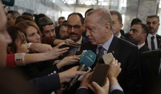 """Turkey's President Recep Tayyip Erdogan speaks to the media at the parliament in Ankara, Turkey, Tuesday, Jan. 8, 2019. Erdogan said Turkey's preparations for a new military offensive against terror groups in Syria are """"to a large extent"""" complete. Erdogan made the comments just hours after U.S. national security adviser John Bolton met with Turkish officials seeking assurances that Turkey won't attack U.S-allied Kurdish militia in Syria. (AP Photo/Burhan Ozbilici)"""