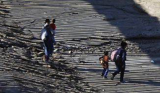 ADDS TO CLARIFY THAT COMPANIES ARE OPPOSING SHAREHOLDER VOTE ON PROPOSAL - FILE - In this Dec. 9, 2018, file photo, the striped shadow of the U.S. border wall falls on a migrant family as they walk on U.S. soil near Imperial Beach, Calif., after squeezing through a small hole under the border wall aided by two local guides, seen from Tijuana, Mexico. The nation's two largest private detention companies don't want a shareholder vote on resolutions that would prevent them from housing immigrant children separated from their parents, even though both companies say that is not something they currently do. (AP Photo/Rebecca Blackwell, File)