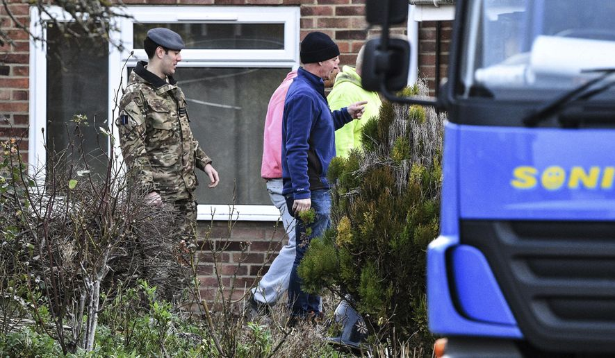 Contractors and military personnel are seen outside the home of former Russian spy Sergei Skripal in Salisbury, England, as scaffolding is delivered Tuesday, Jan. 8, 2019. The house is to be dismantled, with the roof completely removed by military teams, in the wake of the Novichok poisoning attack, as decontamination work continues. (Ben Birchall/PA via AP) ** FILE **