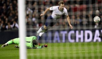 Tottenham's Harry Kane, falls as he challenges, Chelsea's goalkeeper Kepa Arrizabalaga during the English League Cup semifinal first leg soccer match between Tottenham Hotspur and Chelsea at Wembley Stadium in London, Tuesday, Jan. 8, 2019. (AP Photo/Kirsty Wigglesworth)
