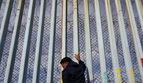 A man holds on to the border wall along the beach, Tuesday, Jan. 8, 2019, in Tijuana, Mexico. (AP Photo/Gregory Bull)