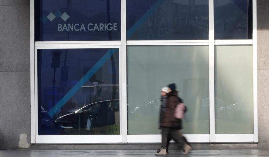 """People walk past a """"Banca Carige"""" bank branch in Milan, Italy, Tuesday, Jan. 8, 2019. Italy's populist government has stepped in to help guarantee struggling Banca Carige SpA, bending to pressure despite the ruling 5-Star Movement's longtime anti-bank bailout rhetoric. In a statement, the government said it passed a decree late Monday that guarantees future bond issues and foresees the possibility of a precautionary public recapitalization. Premier Giuseppe Conte said the measures were aimed at protecting the """"rights and interests"""" of ordinary Carige account-holders. (AP Photo/Antonio Calanni)"""