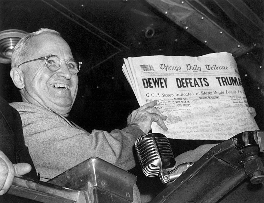 """FILE - In this Nov. 4, 1948, file photo, President Harry S. Truman at St. Louis' Union Station holds up an election day edition of the Chicago Daily Tribune, which - based on early results - mistakenly announced """"Dewey Defeats Truman."""" (AP Photo/Byron Rollins)"""