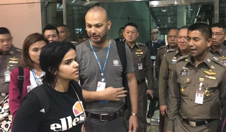 In this photo released by the Immigration Bureau, Saudi woman Rahaf Mohammed Alqunun, foreground walks by Chief of Immigration Police Maj. Gen. Surachate Hakparn, right, before leaving the Suvarnabhumi Airport in Bangkok Monday, Jan. 7, 2019. A Saudi woman who says she is fleeing abuse by her family and wants asylum in Australia has sent out desperate pleas for help over social media. Rahaf Mohammed Alqunun, 18, began posting on Twitter late Saturday after her passport was taken away when she arrived on a flight from Kuwait. (Immigration police via AP)