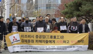 """FILE - In this Nov. 29, 2018, file photo, victims of Japan's forced labor and their family members arrive at the Supreme Court in Seoul, South Korea. A South Korean district court said Wednesday, Jan. 9, 2019, it has decided to freeze the local assets of a Japanese company involved in compensation disputes for wartime Korean laborers. The sign reads """" Mitsubishi Heavy Industries apologize and compensate victims."""" (AP Photo/Ahn Young-joon)"""