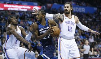 Minnesota Timberwolves forward Andrew Wiggins (22) drives between Oklahoma City Thunder forward Jerami Grant (9) and center Steven Adams (12) in the first half of an NBA basketball game in Oklahoma City, Tuesday, Jan. 8, 2019. (AP Photo/Sue Ogrocki)