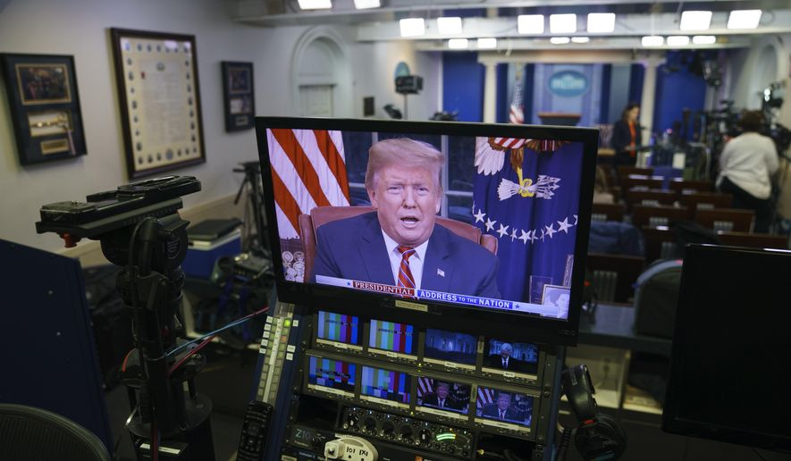 President Donald Trump is seen on monitors in the briefing room of the White House in Washington, as he gives a prime-time address in the Oval Office, Tuesday, Jan. 8, 2019. (AP Photo/Carolyn Kaster)