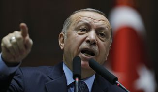 """Turkey's President Recep Tayyip Erdogan gestures as he delivers a speech to MPs of his ruling Justice and Development Party (AKP) at the parliament in Ankara, Turkey, Tuesday, Jan. 8, 2019. Erdogan said Turkey's preparations for a new military offensive against terror groups in Syria are """"to a large extent"""" complete. Erdogan made the comments just hours after U.S. national security adviser John Bolton met with Turkish officials seeking assurances that Turkey won't attack U.S-allied Kurdish militia in Syria. (AP Photo/Burhan Ozbilici)"""