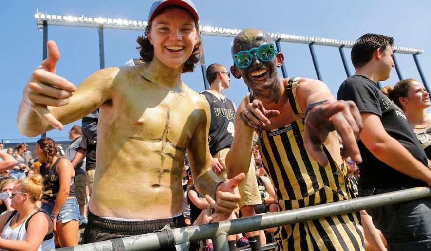FILE - In this Sept. 23, 2017, file photo, freshmen Josh Seals, left, and Tyler Trent, wearing glasses at right, get set for Purdue's NCAA college football game against Michigan at Ross-Ade Stadium, in West Lafayette, Ind. Trent, a former Purdue University student and college football super fan who inspired many with his battle against cancer, died Tuesday, Jan. 1, 2019. He was 20. Funeral service for Trent will be live streamed from College Park Church in Indianapolis, Tuesday, Jan. 8, 2019. (John Terhune/Journal & Courier via AP, File)