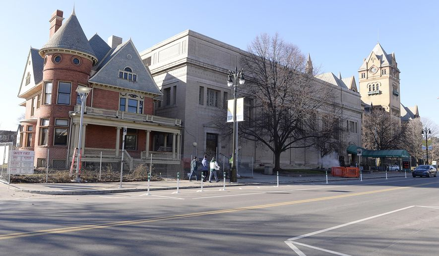 This Friday, Jan. 4, 2019 photo, shows the the 3,000-square-foot David Mackenzie house, left, in Detroit. Wayne State University plans to move the 19th-century Detroit home of its founder to make way for a campus development project. (Clarence Tabb Jr./Detroit News via AP)