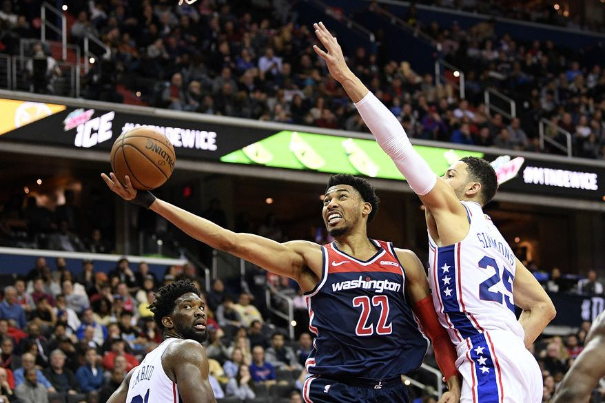 Washington Wizards forward Otto Porter Jr. (22) goes to the basket against Philadelphia 76ers guard Ben Simmons (25) and center Joel Embiid, left, during the second half of an NBA basketball game, Wednesday, Jan. 9, 2019, in Washington. The Wizards won 123-106. (AP Photo/Nick Wass) **FILE**