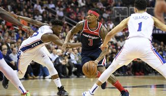 Washington Wizards guard Bradley Beal (3) dribbles the ball between Philadelphia 76ers guard Landry Shamet (1) and guard Jimmy Butler (23) during the second half of an NBA basketball game, Wednesday, Jan. 9, 2019, in Washington. The Wizards won 123-106. (AP Photo/Nick Wass)