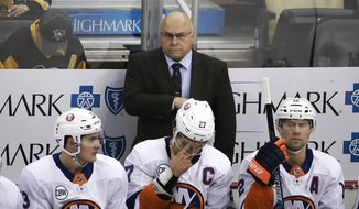 FILE - In this Dec. 6, 2018, file photo, New York Islanders head coach Barry Trotz stands behind his bench during the first period of an NHL hockey game against the Pittsburgh Penguins, in Pittsburgh. Trotz's Islanders are in playoff position and Trotz is also a candidate for the Jack Adams Award. (AP Photo/Gene J. Puskar, File) **FILE**