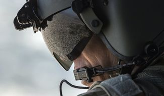 A partial view of  Baghdad is reflected in the visor of a U.S. Army helicopter crew member as he looks out of a Chinook helicopter flying from the U.S. Embassy to Baghdad International Airport, following the helicopter of U.S. Secretary of State Mike Pompeo on Wednesday, Jan. 9, 2019. (Andrew Caballero-Reynolds/Pool Photo via AP)