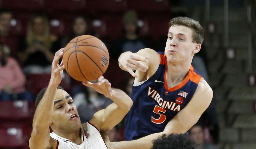Boston College guard Jordan Chatman (25) passes the ball away from Virginia guards Kyle Guy (5) and guard Kihei Clark (0) during the first half of an NCAA basketball game Wednesday, Jan. 9, 2019, in Boston. (AP Photo/Mary Schwalm)