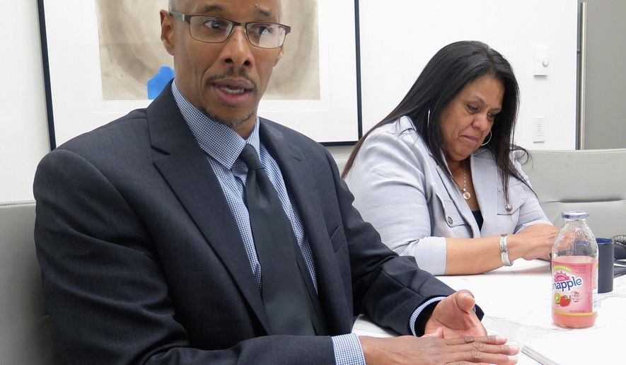 FILE - In this June 28, 2017, file photo, Patrick Pursley, left, talks at his attorney's office in Chicago. Pursley, who has been imprisoned for more than two decades for a murder conviction obtained with shoddy ballistic evidence, is getting a chance to prove his innocence with a new trial. The outcome of the trial that starts Thursday, Jan. 10, 2019, in Winnebago County could help pave a new path to challenge convictions that relied on ballistic analysis once thought to be infallible. He's been free on bail since April 2017. (AP Photo/Ivan Moreno File)