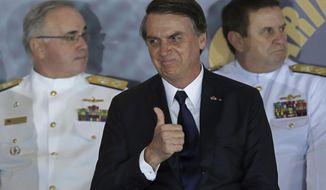 Brazil's President Jair Bolsonaro gives a thumbs up during the inauguration ceremony of the new naval commander, Ilques Barbosa Junior, at the Naval Club in Brasilia, Brazil, Wednesday, Jan. 9, 2019. (AP Photo/Eraldo Peres)