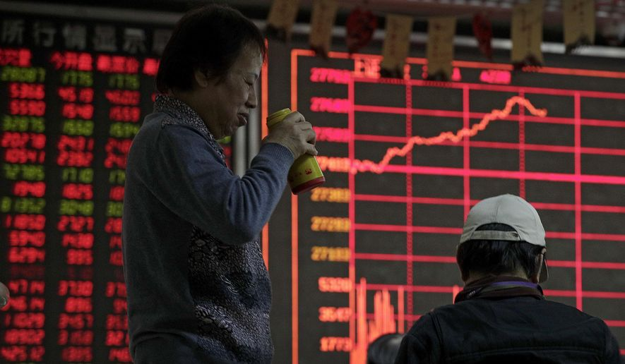 Investors chat as they monitor stock prices at a brokerage house in Beijing, Wednesday, Jan. 9, 2019. Shares extended gains in Asia on hopes for progress in resolving the tariffs battle between the U.S. and China as talks appeared to have been extended in Beijing. (AP Photo/Andy Wong)
