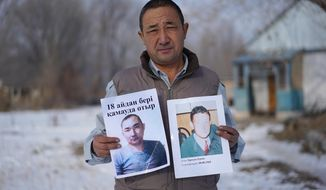 In this Dec. 8, 2018, photo, Adilgazy Yergazy, a farmer, holds up pictures of his detained younger brothers at his home in a village near Almaty, Kazakhstan. The Kazakhstan Foreign Ministry says China is allowing more than 2,000 ethnic Kazakhs to abandon their Chinese citizenship and leave the country, a sign that Beijing may be starting to feel a mounting backlash against a sweeping crackdown on Muslims in its far west region of Xinjiang. Yergazy says two of his little brothers were arrested and taken to internment camps last year, and that one was recently released from the camps but is unable to leave China. (AP Photo/Dake Kang)