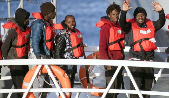 Migrants wave as they disembark at Hay Wharf, Pieta, Malta, Wednesday, Jan. 9, 2019. The 49 rescued migrants who were stranded at sea since last month were brought to Malta and then distributed among eight European Union countries. The deal, announced by Maltese Prime Minister Joseph Muscat, breaks a stalemate that began after 32 were rescued by a German aid group's vessel on Dec. 22. The other 17 were rescued on Dec. 29 by a different aid boat. Both Italy and Malta have refused to let private rescue ships bring migrants to their shores. (AP Photo/Rene Rossignaud)