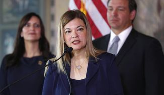 Barbara Lagoa, center, Governor Ron DeSantis' pick for the Florida Supreme Court, speaks after being introduced, as DeSantis and Lt. Gov Jeanette Nunez, left, look on, Wednesday, Jan. 9, 2019, in Miami. (AP Photo/Wilfredo Lee)