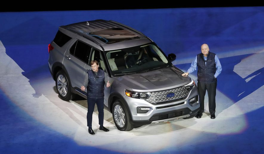 Ford Motor Co., President, Global Markets Jim Farley, left, and President and CEO Jim Hackett stand next to the redesigned 2020 Ford Explorer during its unveiling, Wednesday, Jan. 9, 2019, in Detroit. Ford's aging Explorer big SUV is getting a major revamp as it faces growing competition in the market for family haulers with three rows of seats. (AP Photo/Carlos Osorio)