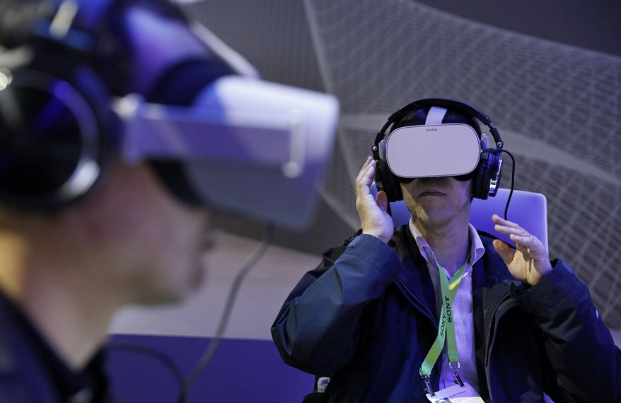 People use Oculus VR headsets at the Panasonic booth at CES International, Tuesday, Jan. 8, 2019, in Las Vegas. (AP Photo/John Locher)