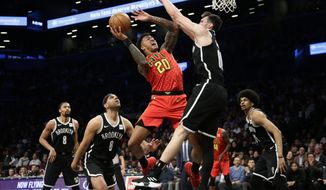 Atlanta Hawks' John Collins (20) shoots as Brooklyn Nets' Rodions Kurucs (00) defends, while Jared Dudley (6) and Spencer Dinwiddie (8) watch during the first half of an NBA basketball game Wednesday, Jan. 9, 2019, in New York. (AP Photo/Frank Franklin II)