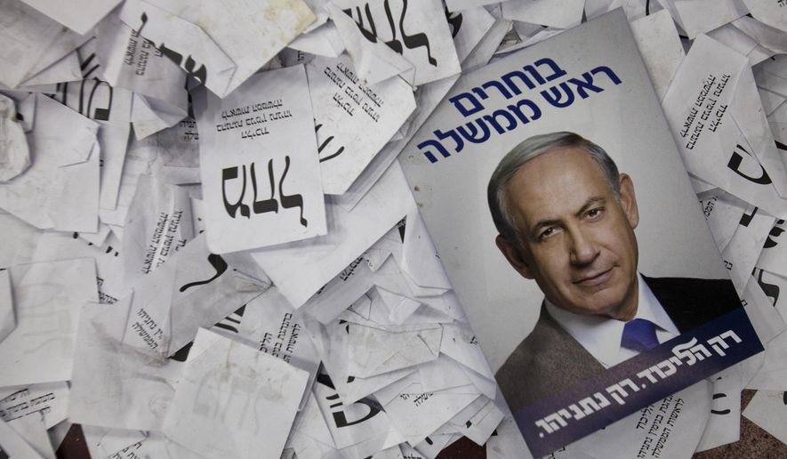 FILE - In this Wednesday, March 18, 2015 file photo, an election campaign poster with the image of Israeli Prime Minister Benjamin Netanyahu lies among ballot papers at his party's election headquarters, in Tel Aviv. Israel's Shin Bet security service says it's able to thwart any foreign intervention in the country's upcoming elections in April 2019, after its director warned of such efforts. ( (AP Photo/Dan Balilty, File)
