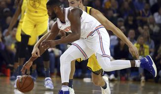 New York Knicks' Emmanuel Mudiay, left, and Golden State Warriors' Klay Thompson chase a loose ball during the first half of an NBA basketball game Tuesday, Jan. 8, 2019, in Oakland, Calif. (AP Photo/Ben Margot)