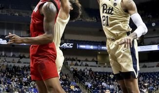 Pittsburgh's Trey McGowens (2) blocks a shot by Louisville's Malik Williams, left, in the first half of an NCAA college basketball game, Wednesday, Jan. 9, 2019, in Pittsburgh. (AP Photo/Keith Srakocic)