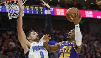 Utah Jazz guard Donovan Mitchell (45) goes to the basket as Orlando Magic center Nikola Vucevic (9) defends during the second half of an NBA basketball game Wednesday, Jan. 9, 2019, in Salt Lake City. (AP Photo/Rick Bowmer)