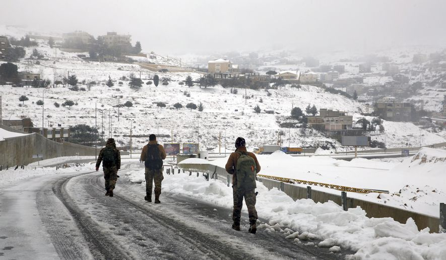 Lebanese soldiers walk on an icy road as they return to their base camp in the village of Sawfar, Mount Lebanon, Wednesday, Jan. 9, 2019. A storm packing snow and rain that has battered Lebanon for five days has left an 8-year-old Syrian girl dead, flooded neighborhoods and paralyzed major mountain roads. (AP Photo/Bilal Hussein)