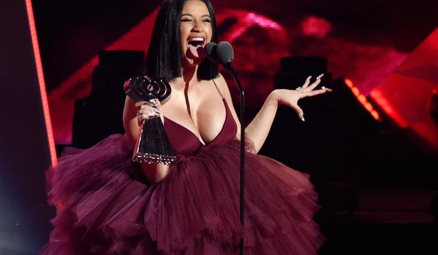 FILE - In this March 11, 2018, file photo, Cardi B accepts the Best New Artist award during the 2018 iHeartRadio Music Awards in Inglewood, Calif. IHeartMedia announced Wednesday that the rapper is nominated for 13 honors at the 2019 iHeartRadio Music Awards. The awards will air live on March 14 from the Microsoft Theater in Los Angeles. (Photo by Chris Pizzello/Invision/AP, File)