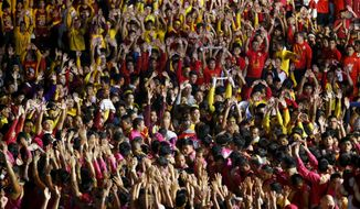 Filipino Roman Catholic devotees raise their hands in prayer as the image of the Black Nazarene is readied for a raucous procession to celebrate its feast day Wednesday, Jan. 9, 2019, in Manila, Philippines. Tens of thousands of mostly barefoot Filipino Catholics joined the annual procession of a centuries-old statue of Jesus Christ to celebrate the Feast of the Black Nazarene which usually ends before dawn the next day. (AP Photo/Bullit Marquez)