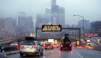 In this photo taken Thursday, Jan. 3, 2019, rush hour northbound Highway 99 traffic backs-up while heading toward the Alaskan Way Viaduct just ahead as a sign overhead advises of an upcoming closure of the roadway in Seattle. The double-decker highway along Seattle's waterfront is set to shut down for good Friday, Jan. 11, ushering in what officials say will be one of the most painful traffic periods in the city's history. The 65-year-old viaduct is being replaced by a four-lane Highway 99 tunnel, scheduled to open several weeks after the viaduct's closure. (AP Photo/Elaine Thompson)