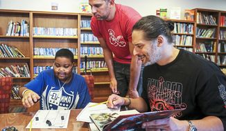 Hospital patient Yaheim Young, 15, of Penn Hills, Pa., left, Nick Manganiello, center, and his brother, Mt. Lebanon native and actor Joe Manganiello, right, count dice as they create their Dungeons and Dragons characters at UPMC Children's Hospital of Pittsburgh Tuesday, Jan. 8, 2019, in the Lawrenceville neighborhood. (Jessie Wardarski/Pittsburgh Post-Gazette via AP)