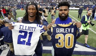 FILE - In this Oct. 1, 2017, file photo, Los Angeles Rams' Todd Gurley, left, and Dallas Cowboys' Ezekiel Elliott, right, swap jerseys after an NFL football game, in Arlington, Texas. Gurley is a big football fan, and Elliott is one of his favorite players. The good feelings are mutual heading into the Cowboys' playoff visit to the Rams and a showdown between the NFL's two premiere running backs. (AP Photo/Michael Ainsworth, File)
