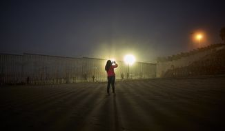 A woman records with her phone, as floodlights from the United States light up the border wall, topped with razor wire, Thursday, Jan. 10, 2019, along the beach in Tijuana, Mexico. Taking the shutdown fight to the Mexican border, U.S. President Donald Trump edged closer Thursday to declaring a national emergency in an extraordinary end run around Congress to fund his long-promised border wall. (AP Photo/Gregory Bull)