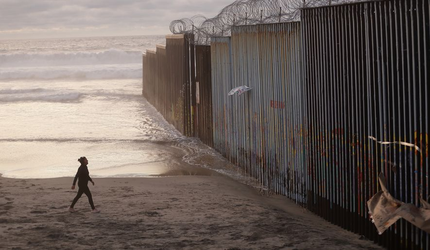 "A woman walks on the beach Wednesday, Jan. 9, 2019, next to the border wall topped with razor wire in Tijuana, Mexico. U.S. President Donald Trump walked out of his negotiating meeting with congressional leaders Wednesday  ""I said bye-bye,"" he tweeted as efforts to end the 19-day partial government shutdown fell into deeper disarray over his demand for billions of dollars to build a wall on the U.S.-Mexico border. (AP Photo/Gregory Bull)"