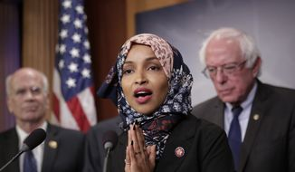 """Freshman Rep. Ilhan Omar, D-Minn., center, joins Rep. Peter Welch, D-Vt., left, and Sen. Bernie Sanders, I-Vt., as Sanders prepares to introduce new legislation to reduce what Americans pay for prescription drugs, especially brand-name drugs deemed """"excessively priced,"""" during a news conference on Capitol Hill in Washington, Thursday, Jan. 10, 2019. (AP Photo/J. Scott Applewhite) ** FILE **"""