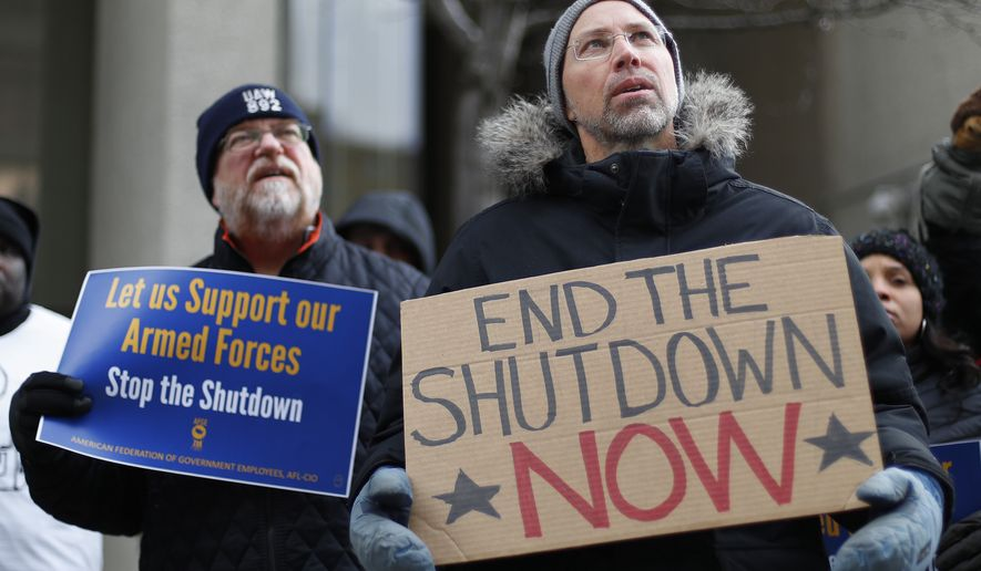 Bryan Manning, right, an Environmental Protection Agency employee, holds a sign at a rally to call for an end to the partial government shutdown in Detroit, Thursday, Jan. 10, 2019. (AP Photo/Paul Sancya)