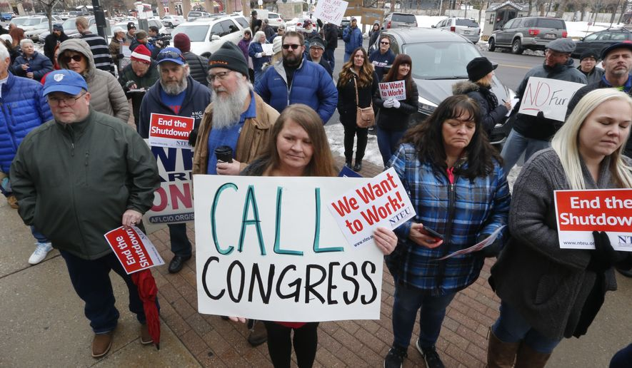 IRS worker Angela Gran, center, and others participate in a federal workers protest rally outside the Federal Building, Thursday, Jan., 10, 2019, in Ogden, Utah. Payday will come Friday without any checks for about 800,000 federal employees affected by the government shutdown, forcing workers to scale back spending, cancel trips, apply for unemployment benefits and take out loans to stay afloat. (AP Photo/Rick Bowmer)