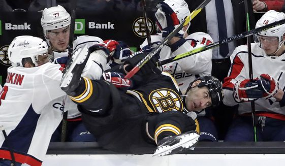 Boston Bruins defenseman Zdeno Chara is checked into the Washington Capitals bench by Washington Capitals left wing Alex Ovechkin, left, during the first period of an NHL hockey game Thursday, Jan. 10, 2019, in Boston. (AP Photo/Elise Amendola)