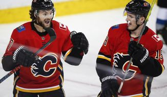 Calgary Flames' Michael Frolik, left, of the Czech Republic, celebrates his goal against the Colorado Avalanche with Matthew Tkachuk during the third period of an NHL hockey game Wednesday, Jan. 9, 2019, in Calgary, Alberta. (Jeff McIntosh/The Canadian Press via AP)