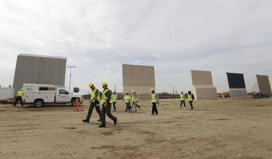 """File - In this Oct. 19, 2017 file photo, people pass border wall prototypes as they stand near the border with Tijuana, Mexico, in San Diego. Montana's Senate president is proposing the state give more than $8 million to help build President Donald Trump's proposed wall on the Mexican border. Scott Sales, a Republican, says his proposal is a """"small token"""" to show border security """"is of vital interest to all citizens regardless of what state they live in."""" (AP Photo/Gregory Bull, File)"""