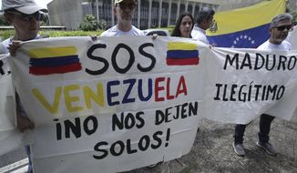 """Venezuelan citizens living in Brazil hold signs that read in Spanish """"S.O.S. Venezuela. Don't leave us alone,"""" left, and """"Maduro. Illegitimate,"""" during protest against the inauguration of Venezuela's President Nicolas Maduro outside Itamaraty Palace in Brasilia, Brazil, Thursday, Jan. 10, 2019. Maduro started a second, six-year term Thursday despite international cries urging him to step down and return democratic rule to a country suffering a historic economic implosion. (AP Photo/Eraldo Peres)"""