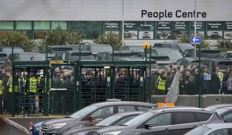 Staff gather inside the gates of the Jaguar Land Rover site in Halewood near Liverpool, England, Thursday Jan. 10, 2019.  According to media reports, Jaguar Land Rover is widely expected to announce up to 5,000 job cuts as the carmaker addresses slowing demand in China and growing uncertainty about the U.K.'s Brexit departure from the European Union. (Peter Byrne/PA via AP)